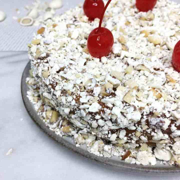 Cake with crushed yogurt covered almonds and cherries on top on a plate with almonds on background