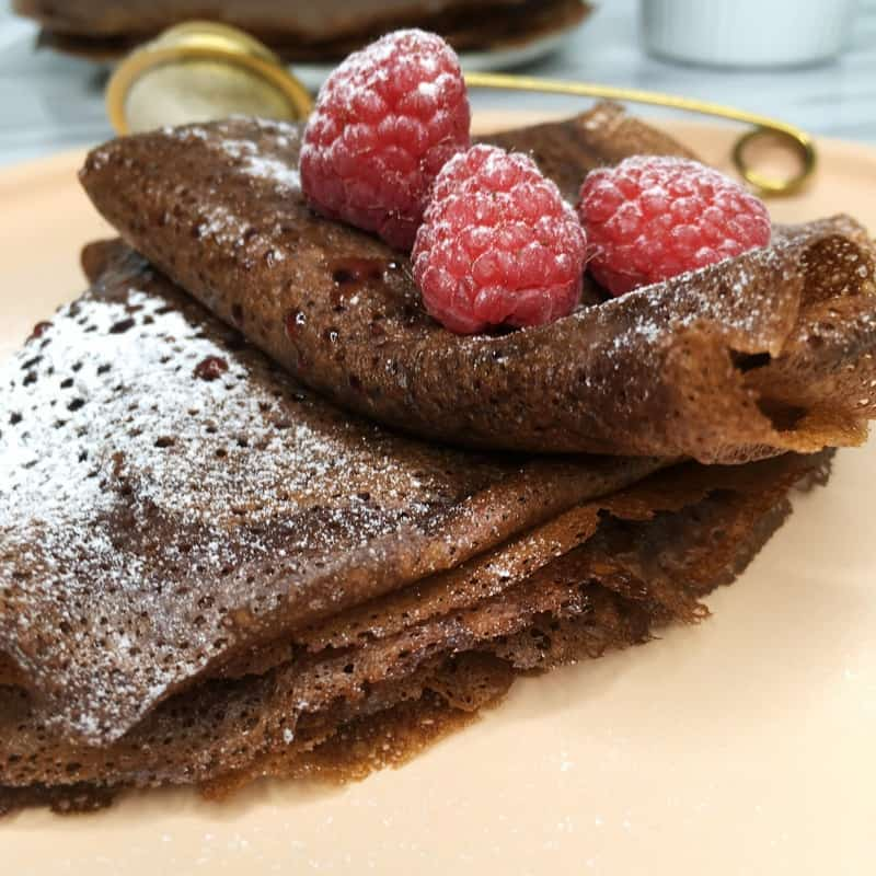 French chocolate crepes folded in four, filled with raspberry jam and dusted with icing sugar and a couple of raspberries on a plate