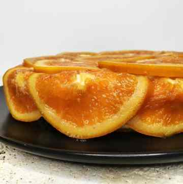 Orange cake served on a black plate: Side view