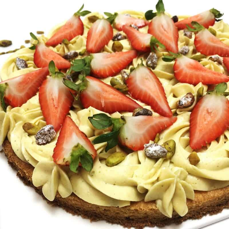 Sable Breton crust topped with greenish mousseline cream, strawberries and sprinkled with pistachios