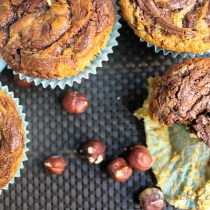 Courgette nutella swirl muffins op donkere placemat met hazelnoten
