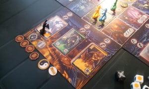 """Il giocatore giallo sta affrontando uno Hunter e altri due demoni; il segnalino bianco e nero rappresenta una risorsa speciale dei monaci, lo Yin-Yang, che può essere spesa per attivare una tessera villaggio qualsiasi in aggiunta alle normali azioni o per """"esorcizzare"""" una tessera del villaggio posseduta dai demoni."""