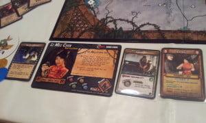 Scheda di un personaggio con a sinistra una carta evento, e a destra una carta Gear (equipaggiamento).