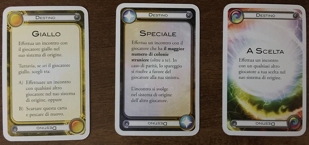 Alcuni esempi di carta destino: quella a sinistra indica di attaccare il giocatore giallo, quella al centro stabilisce una regola per determinare chi attaccare e quella a destra lascia completa libertà di scelta.