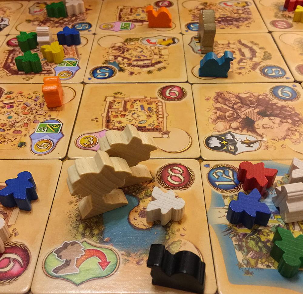 Il giocatore nero ha svuotato la tessere in primo piano nel turno precedente e l'ha occupata con un suo cammello, oltre ad aggiungere una palma bonus come indicato nell'angolo in basso a sinistra.