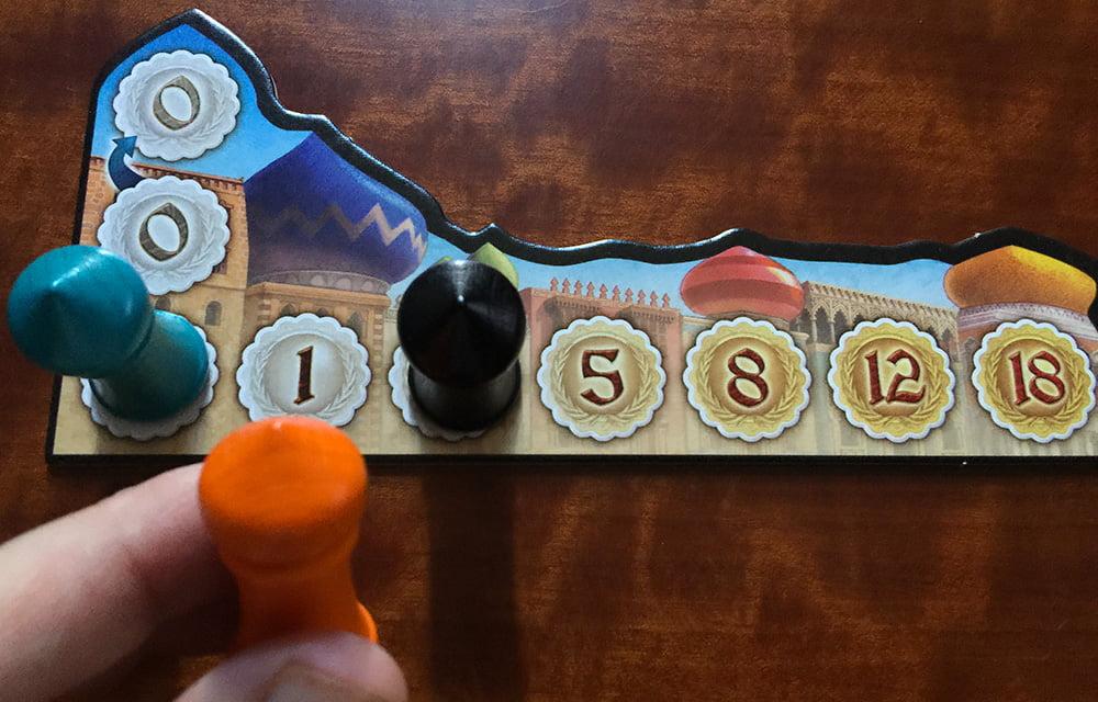 Il giocatore arancione deve decidere se offrire 5 denari per giocare per primo, oppure non offrire nulla e giocare per secondo (perché scalzerà automaticamente il giocatore turchese).