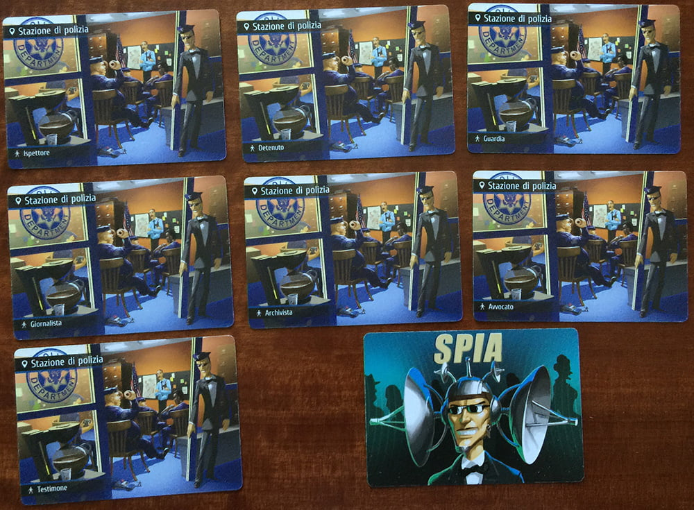 """Le 7 carte che compongono l'ambientazione """"Stazione di Polizia"""", insieme alla carta Spia contenuta nella stessa bustina."""