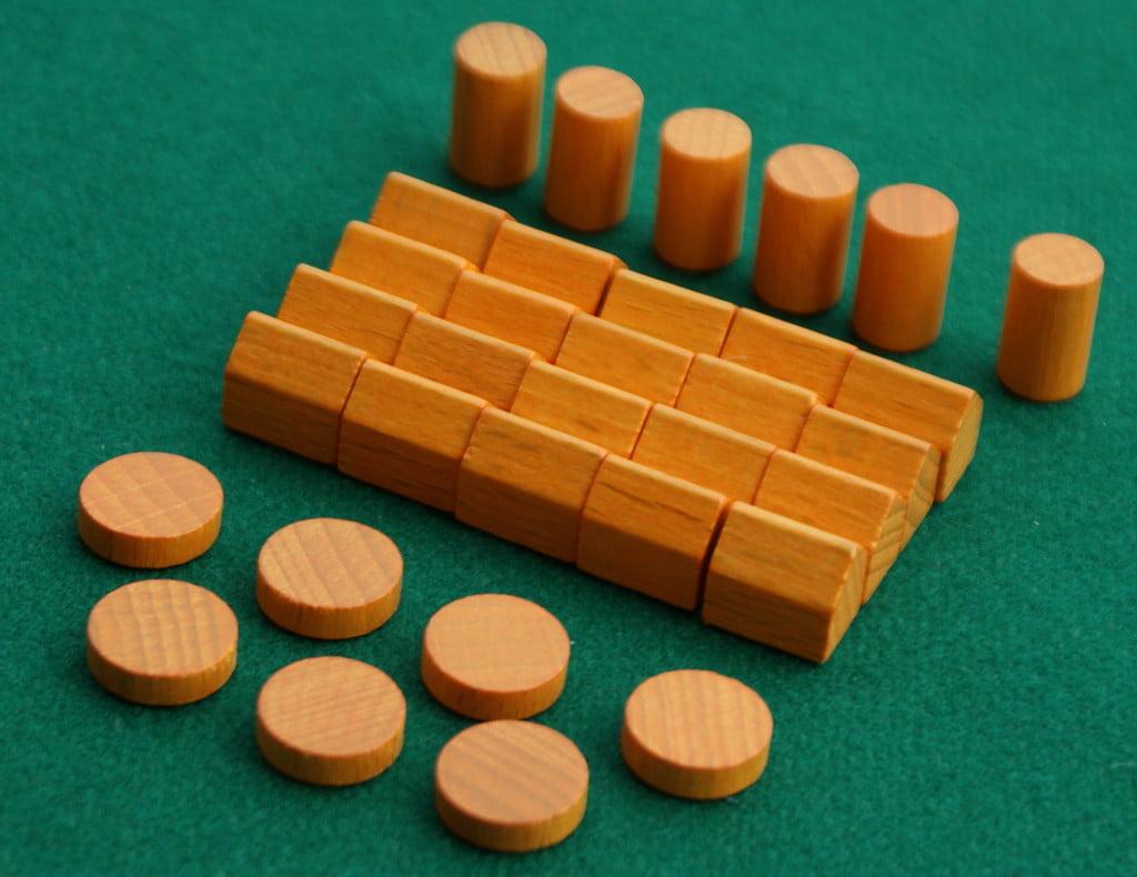 """Questi sono i segnalini che ogni giocatore riceve all'inizio della partita: in primo piano i dischetti """"marcatori"""", poi le casette e, sullo sfondo, i """"lavoratori""""."""
