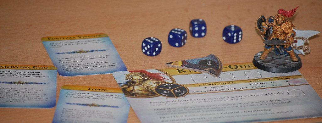 Un personaggio: scheda, miniatura e carte di potenziamento. E, essendo, Warhammer, non potevano mancare i dadi da 6.