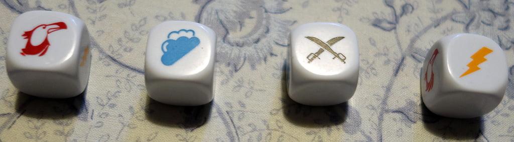 I dadi al centro del gioco: notare i 4 diversi simboli, che contraddistinguono altrettante minacce differenti.