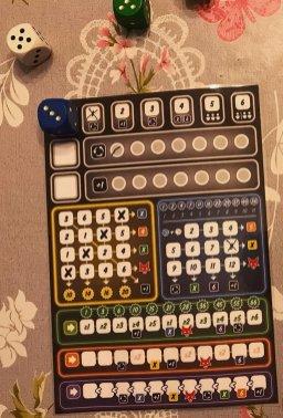 Tra questi, sceglie il 3 blu che, sommato al 5 bianco, gli consente di apporre una crocetta sull'8 nell'area blu. Scarta il dado viola perché di valore inferiore.