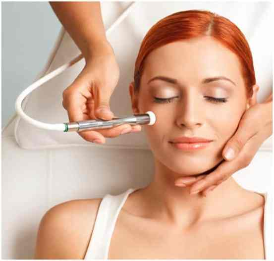 A beautiful women given facial electrical treatment by professional beauty therapy