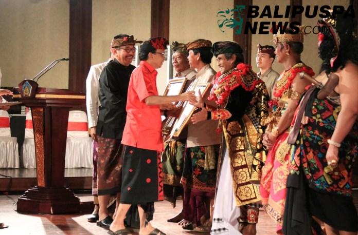 Gubernur Bali Wayan Koster didampingi Wagub Tjokorda Oka Artha Ardhana Sukawati (Cok Ace) dan Ny. Putri Suastini Koster menyerahkan penghargaan bagi pengabdi seni di Gedung Ksirarnawa Taman Budaya Provinsi Bali, Kamis (4/7/2019) petang.