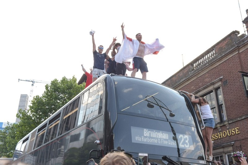 Pic by Michael Scott/Caters News - (PICTURED: England fans on Birmingham's Broad Street take over the road as the celebrate England's win over Sweden. Pic taken 07/07/2018.) - POLICE struggle to keep control as hundreds of England fans take over the roads of Birmingham's Broad Street in the city centre. Several fans were seen on top of a double decker whilst others cheered them on in the jubilant mayhem ENDS
