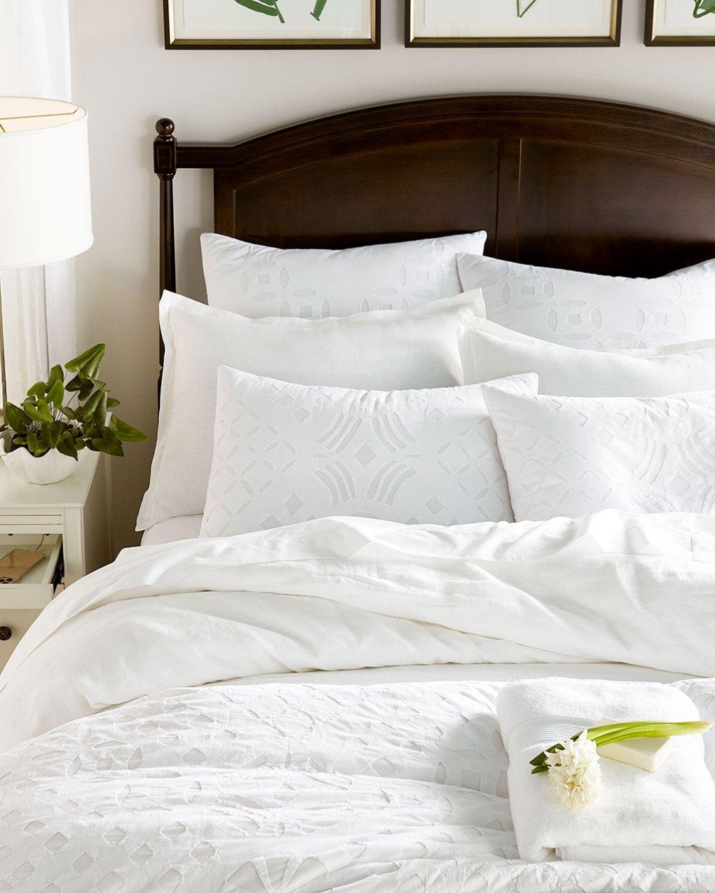Ballard Designs luxurious white bedding in vacation-inspired bedroom