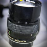 Very cool fixed 135mm lens with f/2.5. It also has a built in hood that slides back out of the way when not needed.