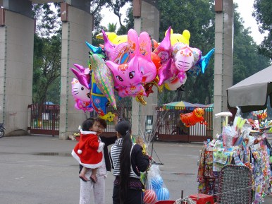 A women buying balloons for a young child