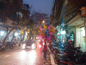 A young girl carrying balloons at night