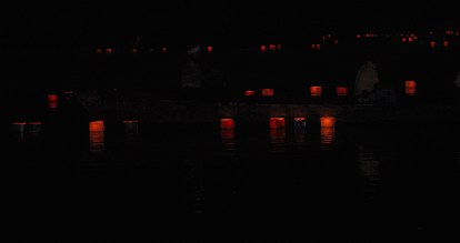 Two men in a boat putting the lanterns in the pond.