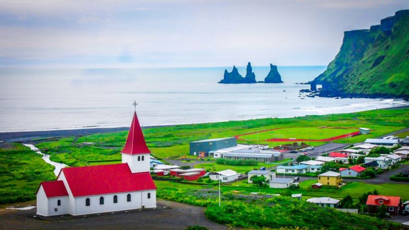 Reynisdrangar (the 3x sea stacks off the coast) and Reynisfjall (mountain in background) as viewed from Vik (town).