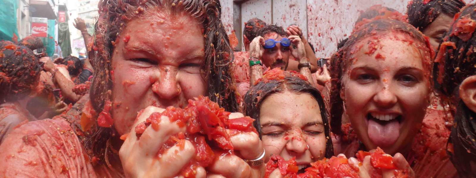 Three young women covered in tomatoes at La Tomatina food festival in Spain.