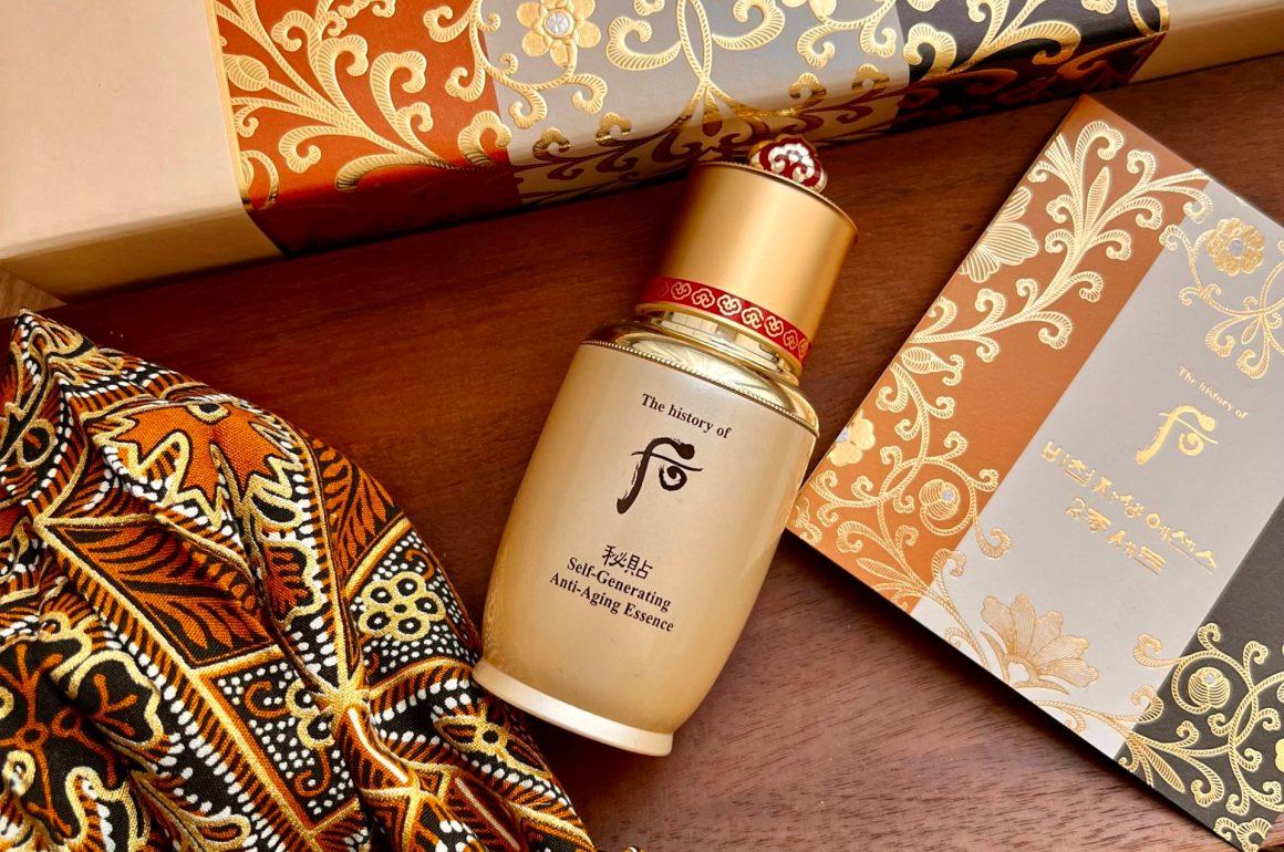 Envase de la esencia de lujo de la marca History of Whoo, en el medio de la imagen y con su caja dorada encima del producto. En la parte inferior de la imagen hay un pañuelo de seda con los mismos tonos que la caja.