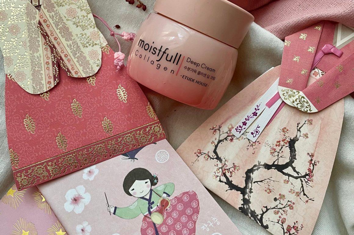 En el centro de la imagen encontramos la crema antiarrugas de Etude House. A los lados del cosmético hay unos recortables en papel del traje tradicional coreana para las mujeres: el hanbok. En la parte inferior de la image hay un cuaderno con una ilustración de una niña llevando un hanbok.