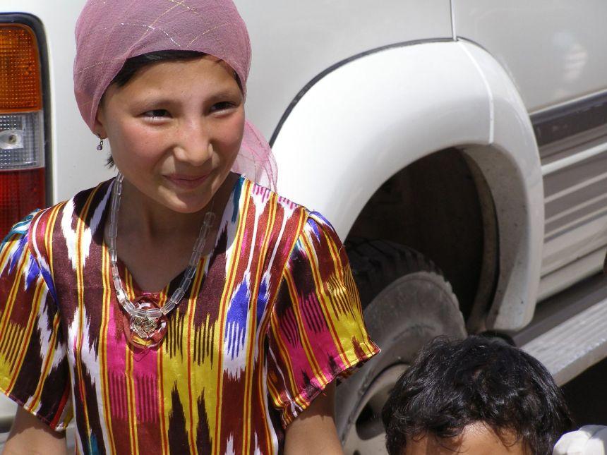 Uighurische Frau mit typischer Kleidung. Ikat.