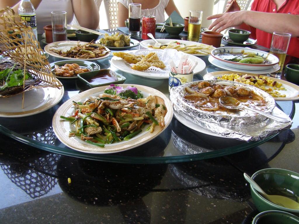Chinesisch Essen am runden Tisch, es wird üppig aufgetischt.