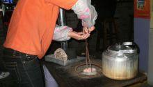 Ein Kohlestaubbrikett wird in den Ofen gesetzt 2009