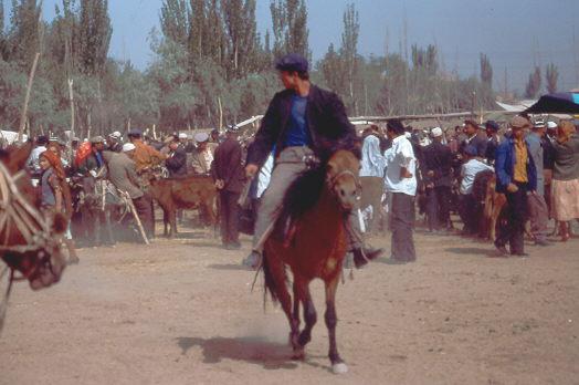Sonntagsmarkt in Kashgar 1992, ein Reiter zeigt das Können seines Pferdes.