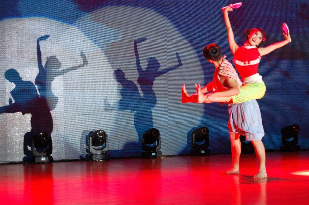 Auf der Bühne, junger Mann trägt Mädchen mit ungebundenen Füßen.