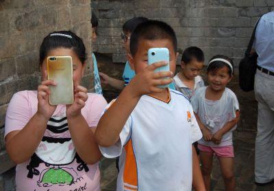 Authentisches Reisen - selbst auf dem Dorf in China haben die Kinder ein Smartphone
