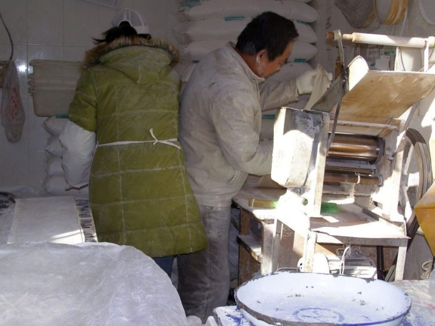 In einem Nudelshop in Peking werden Nudeln mit einer Maschine hergestellt.