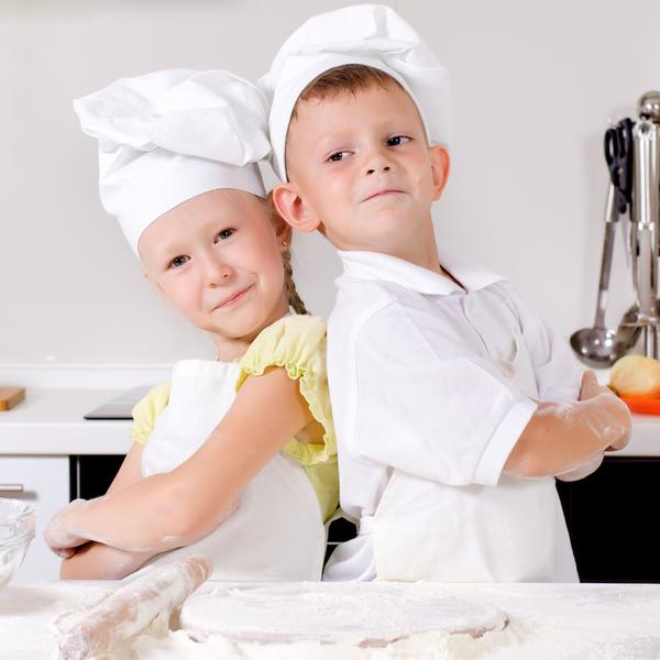 Two cute proud young chefs with a little boy and girl standing back to back in the kitchen in their white uniforms and toques with folded arms smiling at the camera