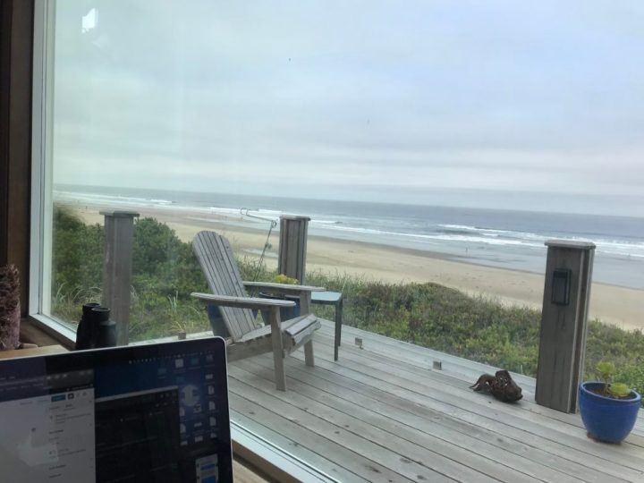 The view out the bay window, overlooking the deck and deck chair. The beach and Pacific Ocean is beyond the deck.