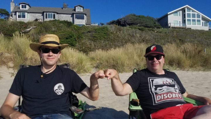 A picture of Max and Brian (the author), sitting on the beach, smiling, bumping fists.