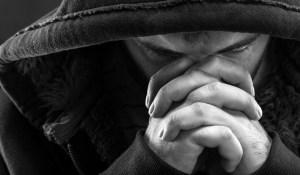 man in hoody praying - background