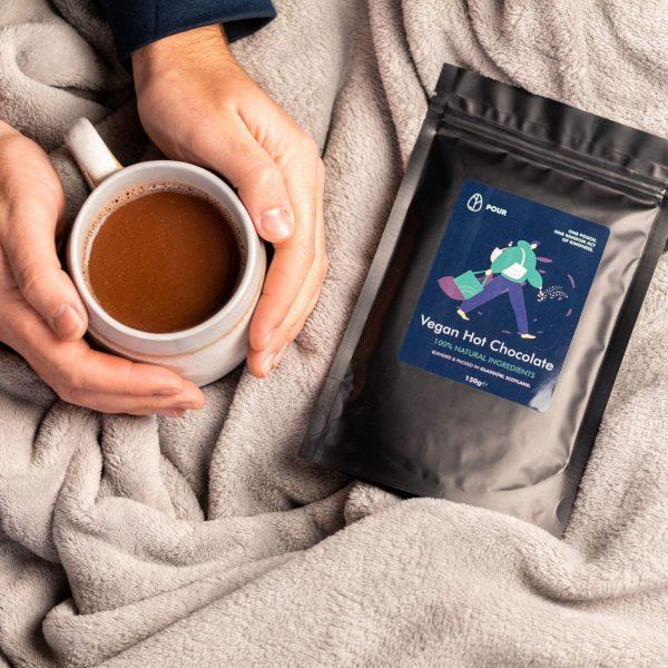 Hands holding mug of Pour Vegan Hot chocolate