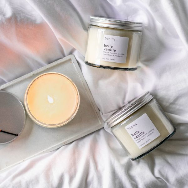Belle vanille candles on bed with one candle lit on concrete tray