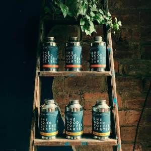 Tins of The Good Coffee Cartel coffee on wooden ladder