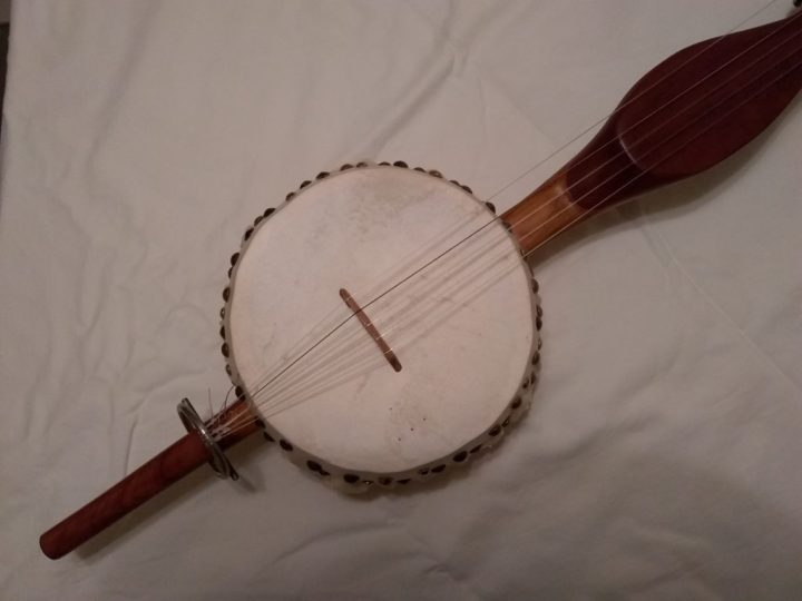 A gourd banjo with a steel ring tailpiece.