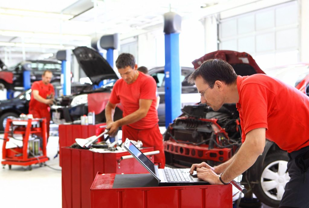 Garage insurance workers compensation coverage. Group car mechanics performing maintenance.