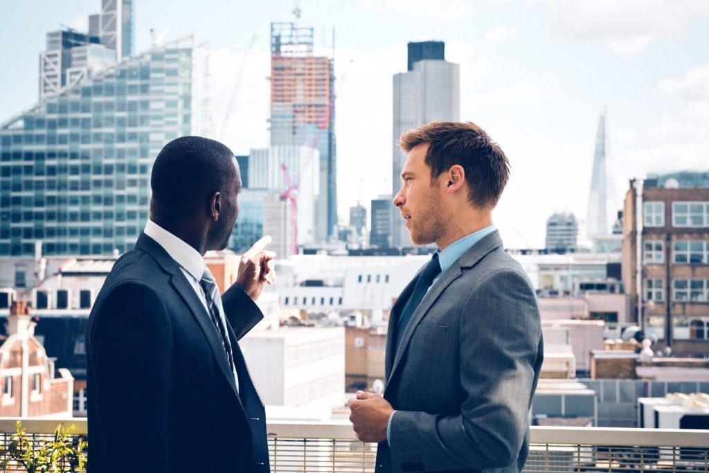Property Management Insurance landlord client building coverage. Two businessmen in suits overlooking cityscape pointing to managed properties.