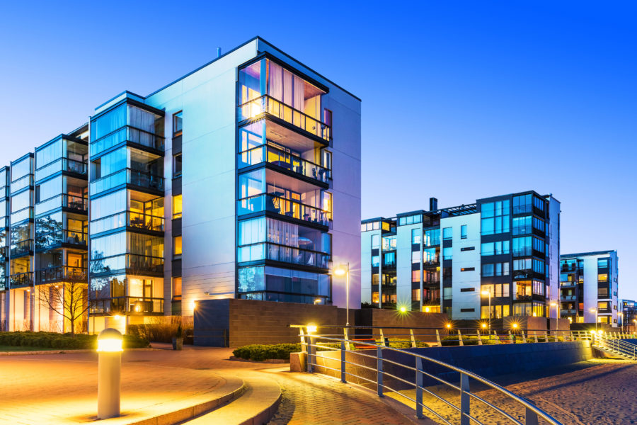 Hotel insurance property coverage. A five story, modern hotel building in evening light shown against a blue sky.