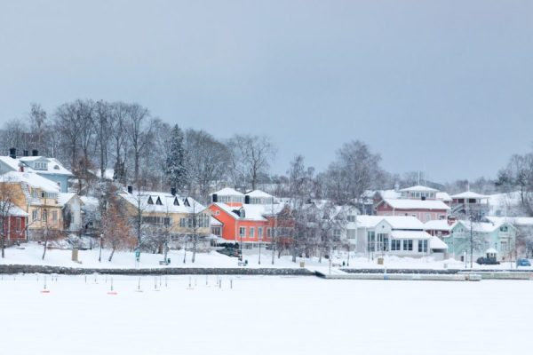 Winter weather claim prevention, houses near frozen lake covered in powdery snow.