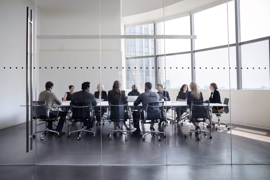 Financial institutions insurance liability, board of directors at business meeting in modern conference room as seen through glass doors.