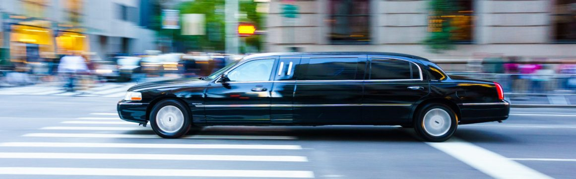 Livery insurance limo header, a black limousine driving in Manhattan, blurred background.
