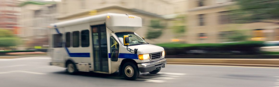 Public transportation insurance NEMT header, a small non-emergency transportation bus on a city street with motion blur background.