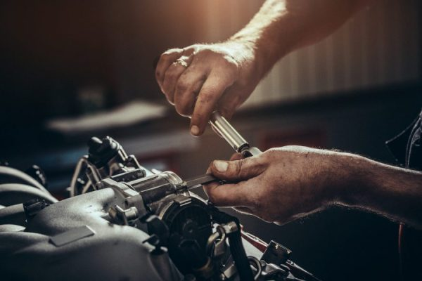Auto repair shop safety, mechanic installs mass air flow sensor. Finger shows wedding ring, a safety breach.